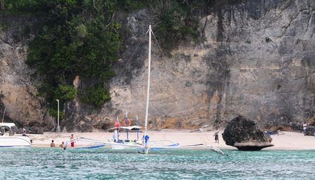 Boracay, Philippines - Feb 1, 2015. Tourists and traditional boat at White beach, Boracay Island, Philippines. photo