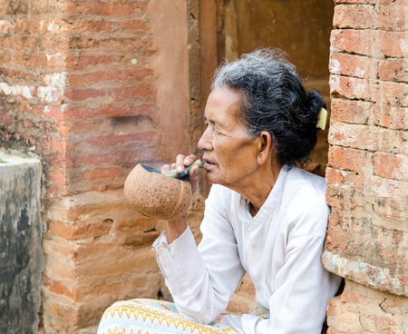 cheroot: Bagan, Myanmar, March 26, 2014. Asiatic old woman smoking a big handmade cigar in Bagan, Myanmar.
