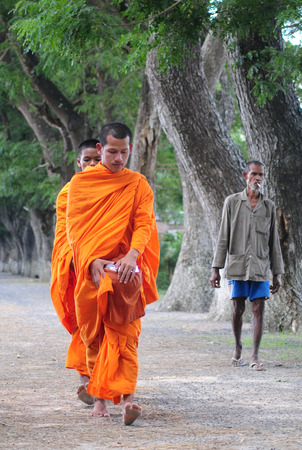 alms: AN GIANG, VIETNAM - FEB 26 2015. Unidentified young monks walking morning alms in An Giang, Vietnam. Theravada Buddhism arrived from India into the southern Vietnam between 300-600 AD. Editorial