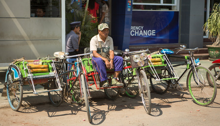 ethnically diverse: YANGON, MYANMAR - FEBRUARY 10, 2015. Burmese street scene with rickshaw in Chinatown in Yangon. Myanmar is ethnically diverse with 51 million inhabitants belonging to 135 ethnic groups. Editorial