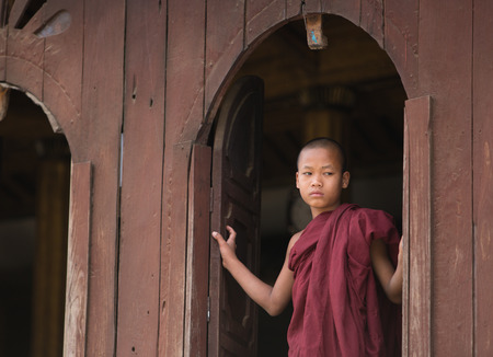 ongoing: MANDALAY, MYANMAR - DECEMBER 8, 2014. An unidentified Burmese Buddhist novice in Mandalay, Myanmar. In 2012 an ongoing conflict started between Buddhists and Muslims in Myanmar.