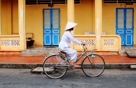 베트남 여자가 베트남 호이에서 자전거 타기. 유네스코 세계 문화 유산 인 호 이안 (Hoi An)은 중부 베트남의 주요 관광지입니다.