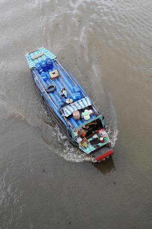 vietnamese ethnicity: MEKONG DELTA, VIETNAM - JUN 23, 2014: Unidentified local Vietnamese man rides the boat at Cai Be Floating Market in Mekong Delta. Editorial