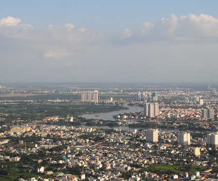 HO CHI MINH CITY (SAI GON), VIET NAM - SEP 15, 2014. Development of modern city with row of highrise buidling rise up to sky and new urban with villas along river in Ho Chi Minh, Vietnam.
