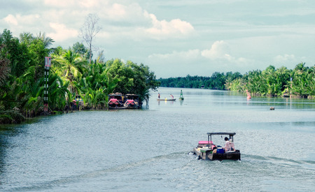 freshwater sailor: Vietnamese man rides a boat over the Mekong river. Mekong is the 12th longest river in the world.