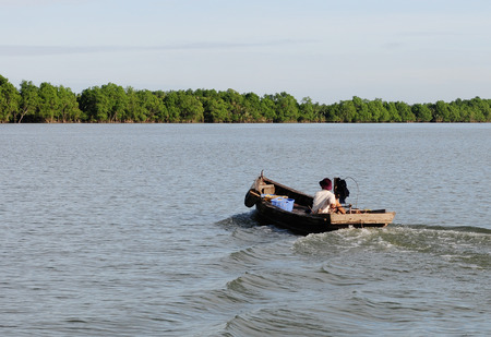 Vietnamese man rides a boat over the Mekong river. Mekong is the 12th longest river in the world.