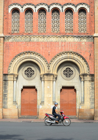 domination: SAIGON, VIETNAM - OCT 2, 2014. People and vehicles around Notre Dame cathedral in Saigon (Ho Chi Minh City), Vietnam. Built in French domination (1880) and designed by architecter J. Bourard.