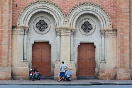 domination: SAIGON, VIETNAM - 02 de octubre de 2014. Las personas y veh�culos en todo catedral de Notre Dame en Saig�n (Ho Chi Minh), Vietnam. Construido en la dominaci�n francesa (1880) y dise�ado por architecter J. Bourard. Editorial