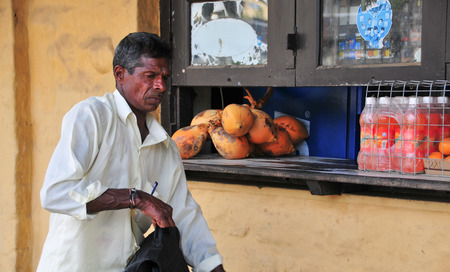 sunday market: HIKKADUWA, SRI LANKA - FEBRUARY 23, 2015. Portrait of elderly market vendor selling his produce. The Sunday market is great way to see Hikkaduwas local life.