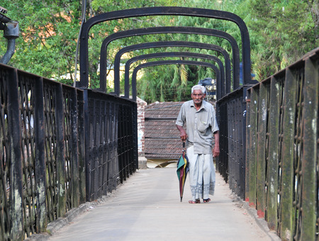 largest: COLOMBO, SRI LANKA - MAY 2, 2014. An unidentified man walking and relaxing at the park in Colombo. Colombo is the largest city with population about 1 million people.