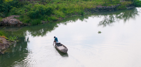 poisoned: Mekong Delta Vietnam  Mar 13 2011. A man sitting on small boat harvesting vegetables on river in Mekong Delta southern Vietnam. Editorial