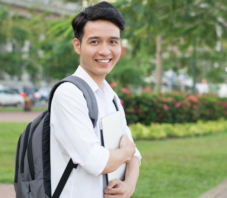 公園でのラップトップでアジアの学生