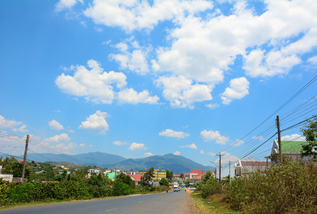 loc: Mountain road at sunny day with clouds on the sky in Dalat highland, Vietnam. Stock Photo
