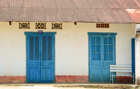 Old house wall with blue door and window in Dalat, Vietnam. photo