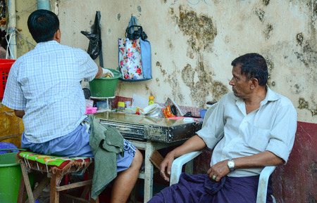 intoxicate: YANGON, MYANMAR - JAN 30, 2015. Busy street vendor selling breakfast and betel leaves at Yangon bus station in Myanmar (Burma).