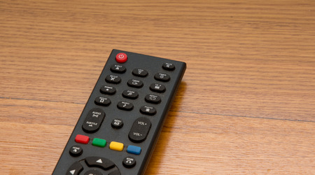 television remote: TV (television) remote on the wooden desk Stock Photo