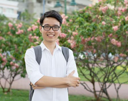 그의 웃는 얼굴, 자연 배경으로 젊은 아시아 학생 임원 스톡 콘텐츠