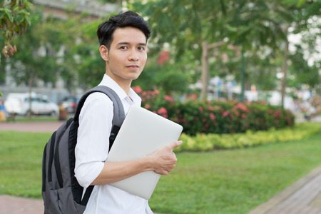 Aziatische student met laptop in het park Stockfoto