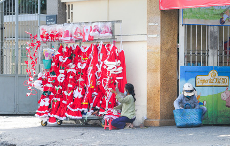 merchant: Saigon, Vietnam - Dec 17, 2013. Merchant selling Noel clothings on street in Saigon downtown, Vietnam.