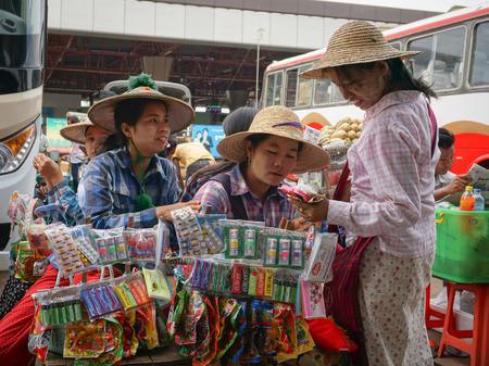 trifles: YANGON, MYANMAR - MARCH 10, 2015. Unidentified street pedlars selling local souvenirs have a chat in Yangon downtown, Myanmar. Editorial