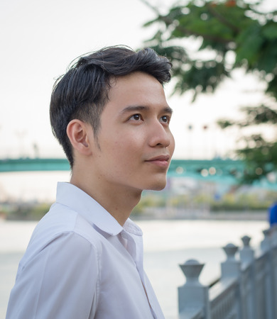 adult vietnam: Portrait of young handsome man of Asian thinking and watching. Stock Photo