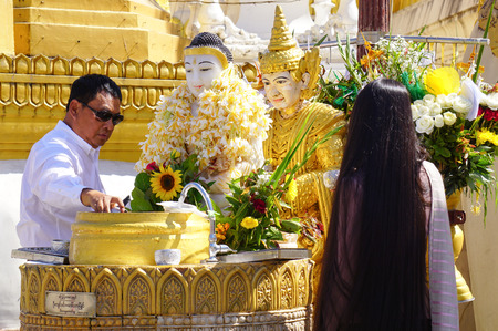 blessings: Yangon Myanmar Buddhist devotees bathing Jan 15 2015 Buddha statue at Shwedagon Pagoda for blessings in Yangon Myanmar Burma. Editorial