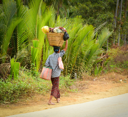 impoverished: NGAPALI MYANMAR  JANUARY 18 2015. A woman is carrying a bag on her head walking on the street in Ngapali Myanmar Burma.