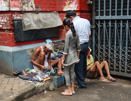 penury: KOLKATA, INDIA - JUL 8, 2015. Unidentified shoe shiner does his job at street of Kolkata. Lots of people make their living by doing this job in India. Editorial