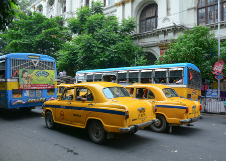 ambassador: KOLKATA, INDIA - JUL 8, 2015. Yellow Ambassador taxi cars go on the street in Kolkata, India. First Ambassador was produced by the Yellow Cab Manufacturing Company in 1921.