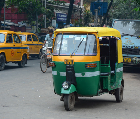 auto rickshaw: KOLKATA, INDIA - JUL 8, 2015. Private auto rickshaw three-weeler tuk-tuk taxi drives down the street in Kolkata. Indian three-wheelers have the design of the Piaggio Ape C, from 1948.