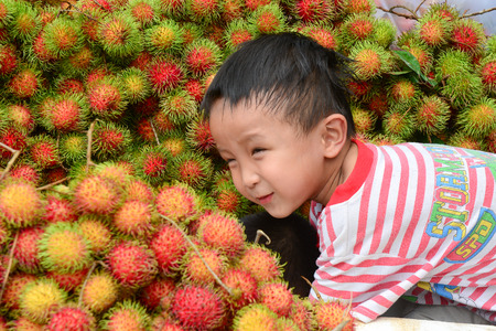 identified: Mekong Delta, Vietnam - Jun 25, 2015. An identified boy playing with many rambutan fruits at a market in Mekong Delta, Vietnam.