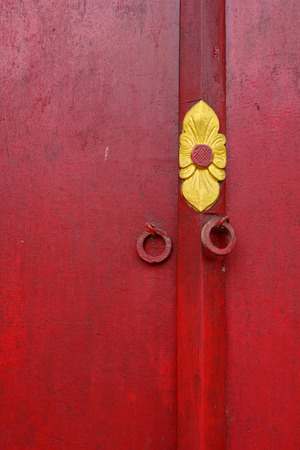 future buddha: Red wooden door with texture and scratch at Khmer temple in Mekong Delta, southern Vietnam.