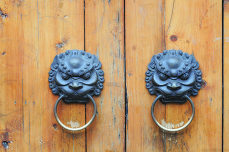 animal private: Lion hand grips on wooden Chinese door in Chengdu, Sichuan.
