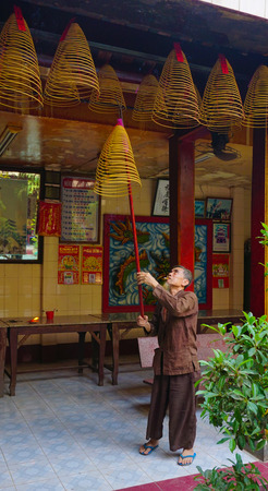 jade buddha temple: Saigon, Vietnam - May 22, 2015. An unidentified man offering incense sticks for the Gods in the Vietnamese Jade Emperor Pagoda in Ho Chi Minh city (Saigon), Vietnam.