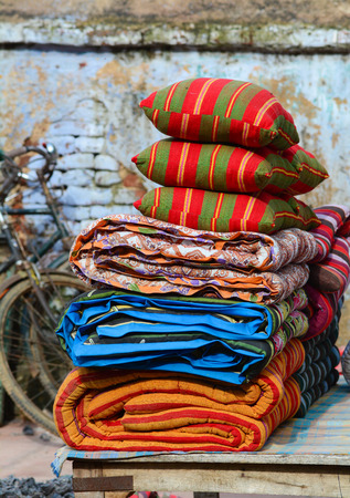 gaya: A pile of multicolored rugs and cushions in outdoor, Gaya, India.