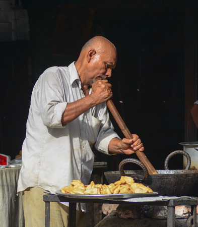 priced: DELHI, INDIA - JUN 16, 2015. Unidentified market vendor selling food in a local restaurant in Delhi, India. Street foods in India are reasonably priced and easily available.