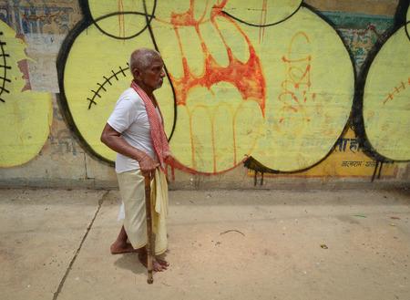 varanasi: Varanasi, India - Jul 12, 2015. An unidentified Indian man wearing traditional clothing walking at the ghats on the banks of Ganges river in Varanasi, India.