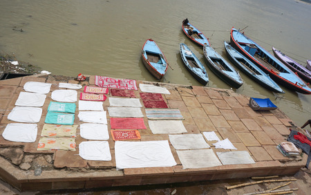 benares: Varanasi, India - Jul 12, 2015. Local people doing their daily activities by the River Ganga at the Assi Ghat, including drying their clothes. Ghats of Varanasi serves many purposes. Editorial