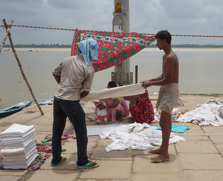 pilgrim journey: Varanasi, India - Jul 12, 2015. Local people doing their daily activities by the River Ganga at the Assi Ghat, including drying their clothes. Ghats of Varanasi serves many purposes. Editorial