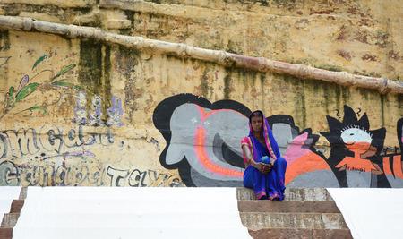 varanasi: Varanasi, India - Jul 12, 2015. An Indian woman in traditional sari sitting at the ghat in Varanasi, India. Silk weaving is the dominant industry in Varanasi.