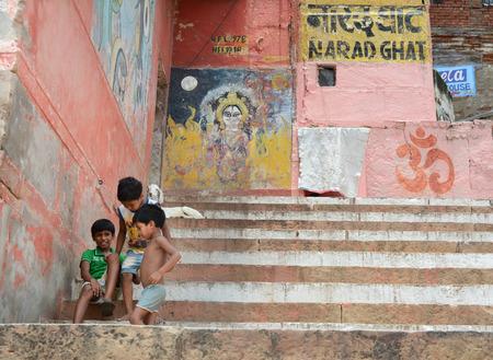 indian village: Varanasi, India - Jul 12, 2015. Unidentified young boys in an Indian village happily sitting on steps and looking at camera, Varanasi, India.