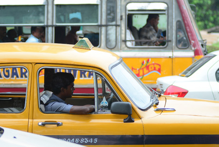 ambassador: KOLKATA, INDIA -  AUG 2, 2015. Taxi driver in the car. The classical ambassador cab is the unique style of taxi service that imported from British civilization in Kolkata, India. Editorial