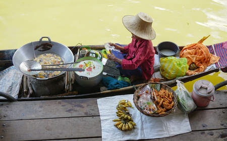 famous women: Bangkok, Thailand - May 22, 2015. Thai women selling fresh fruits on the Damnoen Saduak floating market in Thailand. This is the most famous of the floating markets in Thailand. Editorial