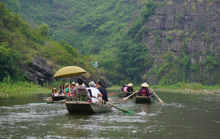 tam: Tam Coc, Vietnam - Sep 3, 2015. People rowing boats for carrying tourists on Ngo Dong river of the Tam Coc National Park. Tam Coc is a popular tourist destination near the city of Ninh Binh in northern Vietnam.
