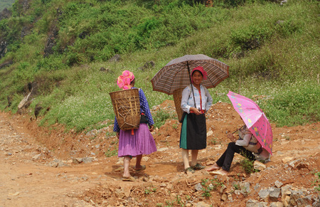 coming home: HA GIANG, VIETNAM - SEP 2, 2015. People walking on countryside road to coming home after finish work in Ha Giang, north of Viet Nam.
