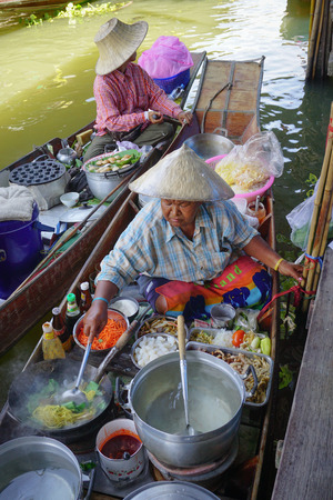 famous women: Bangkok, Thailand - May 22, 2015. Thai women cooking foods for sale on the Damnoen Saduak floating market in Thailand. This is the most famous of the floating markets in Thailand. Editorial