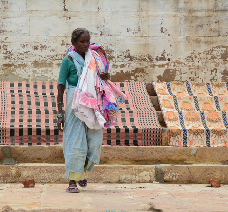 benares: Varanasi, India - Jul 12, 2015. An Indian woman doing her daily activities by the River Ganga at the Assi Ghat, including drying their clothes. Ghats of Varanasi serves many purposes.
