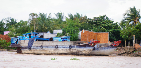 tributary: Can Tho, Vietnam - August 12, 2015. Wooden river boats on a tributary of the Can Tho River on the outskirts of Can Tho in the Mekong Delta region of Vietnam.