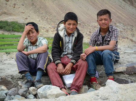 Leh, India - Jul 22, 2015. Group of Tibetan chidren sitting together on the road to Nubra Valley, India. 65% of children attend school, but absenteeism of both students and teachers remains high.