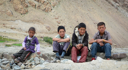 absenteeism: Leh, India - Jul 22, 2015. Group of Tibetan chidren sitting together on the road to Nubra Valley, India. 65% of children attend school, but absenteeism of both students and teachers remains high.